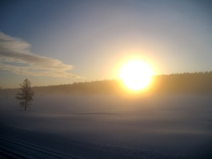 Aurinko ja luminen maisema.