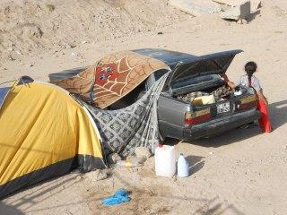 Auto ja teltta ja niiden väliin viritetty kangas.