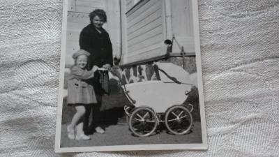 Valokuvassa vanhat vaunut, tytär ja äiti.