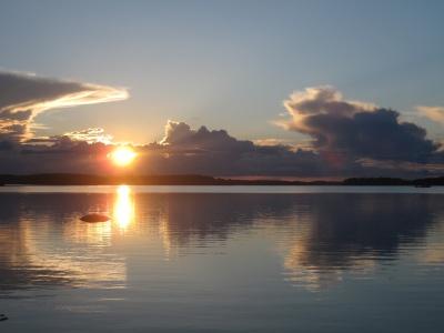 Aurinko kumartaa kohti horisonttia järveltä päin kuvattuna.