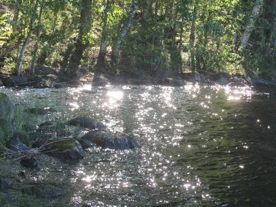 Auringonsäteet osuvat veden pintaan.