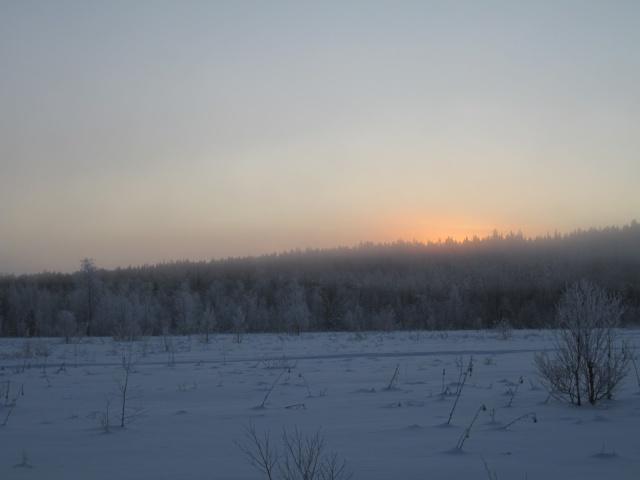 Aurinko laskee lumisen maiseman ylle,