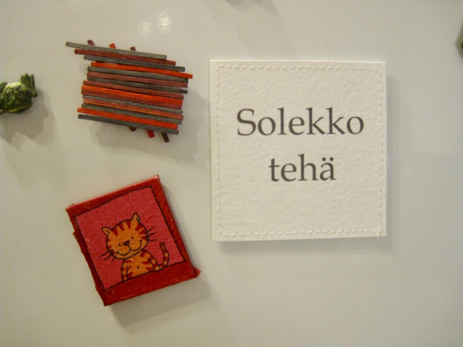 """Huovutettuja kangaslappuja pöydällä, jossa yhdessä lukee """"Solekko tehä""""."""