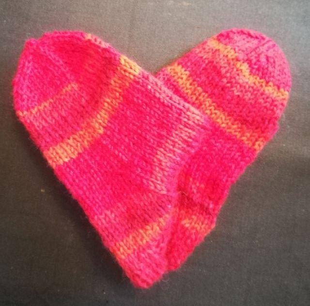 Kaksi punaista villasukkaa on asetettu päällekkäin niin, että niiden terät muodostavat sydämen kuvan..