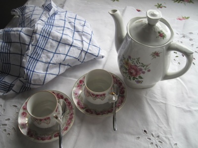 Ruusuisia kahvikuppeja ja kannu pöydällä.