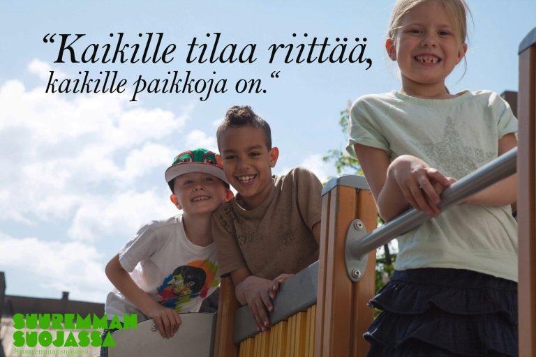 """Suuremman suojassa -verkkosivuston kortti, jossa lukee """"Kaikille tilaa riittää, kaikille paikkoja on"""". Kortissa on kaksi poikaa ja tyttö, jotka hymyilevät leikkikentällä kameralle."""