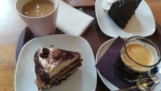 Kaksi kahvikuppia ja kaksi leivosta pöydällä.