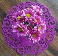 Violetteja kukkasia violetilla pöytäliinalla.