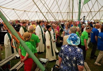 Pappeja kulkemassa ihmisten joukossa käytävää pitkin isossa teltassa Kansan Raamattuseuran Sanan Suvipäivillä Kangasniemellä.