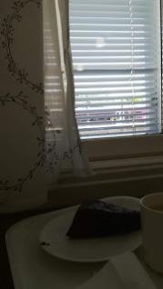 Pöydällä kahvikuppi ja leivos.