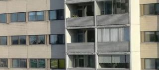 Kerrostalon ikkunoita ja parvekkeita.