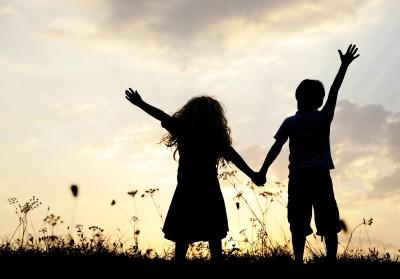 Pienet tyttö ja poika pitävät toisiaan niityllä kädestä kiinni.