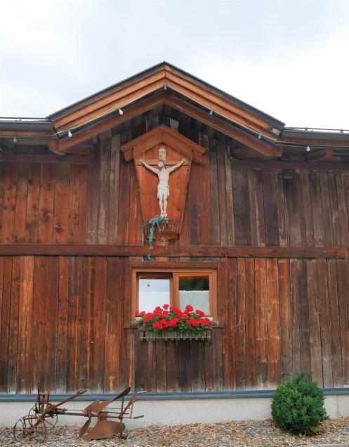 Talo, jonka päädyssä on Jeesus ristillä.