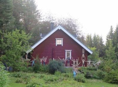 Parikkalan patsaspuiston patsaita ja punainen talo taustalla.
