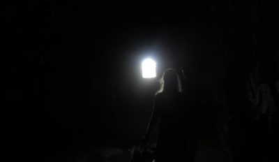 Muuten pimeää, mutta nainen pitää lyhtyä kädessään, josta loistaa valo.