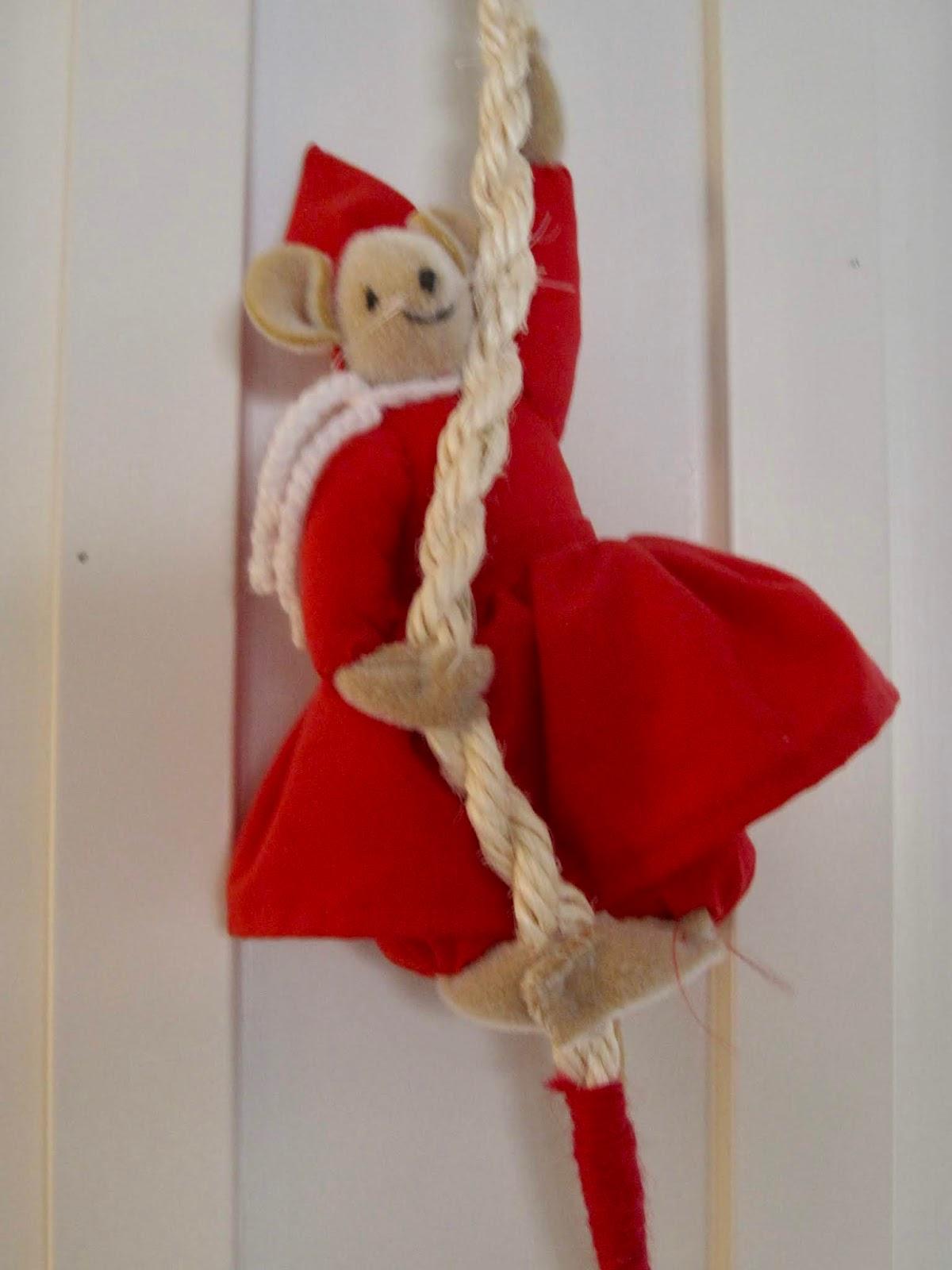 Hiirijoulukoriste, jolle on puettu punainen mekko ja joka roikkuu köydestä.