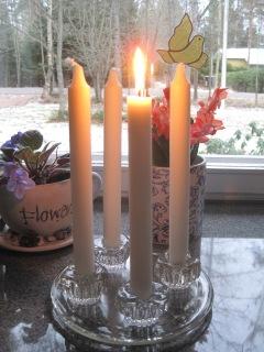 Neljä kynttilää, joista yksi on sytytetty.