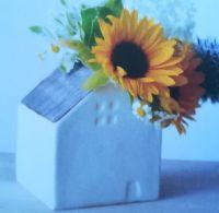 Talonmuotoinen kukkamaljakko, jossa on auringonkukkia.