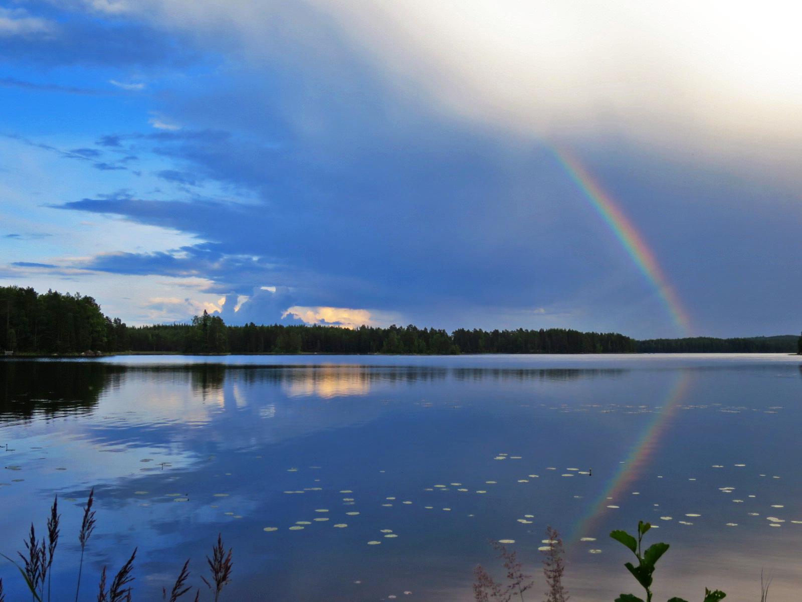 sateenkaari sinisellä taivaalla ja heijastumana järvessä.