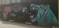 Hieno graffittiteos, jossa virtahepo avaa suunsa ja sinne ammutaan tykillä ruokaa.