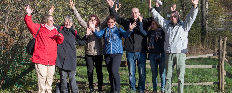Seitsemän blogin kirjoittajaa nostavat molemmat kätensä ylös Keravan seurakuntakeskuksen pihapiirissä.