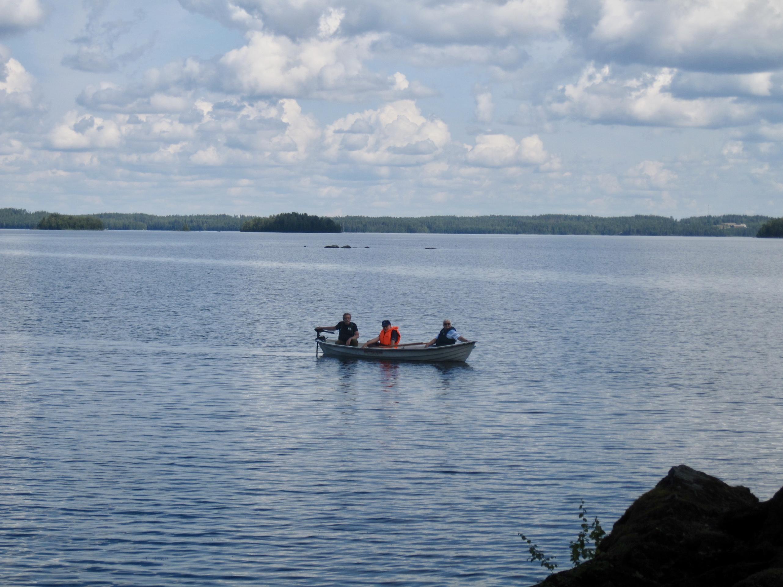 Kolme soutajaa järvellä soutuveneessä.