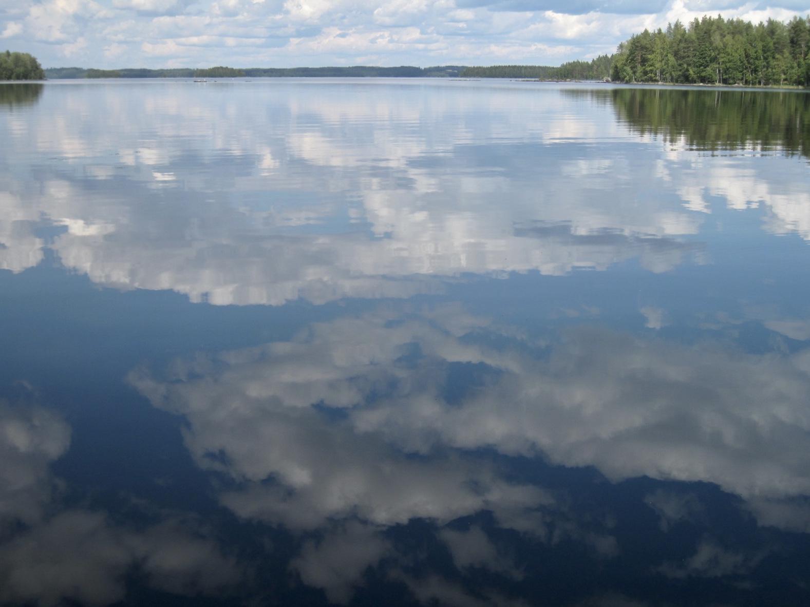 Järven pintaan heijastuvia pilviä.