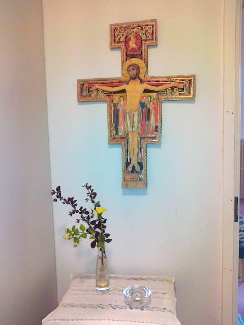 Seinässä ikonimaalaus, jossa Jeesus on ristillä. Pöydällä on maljakossa kukkia ja kynttilä.