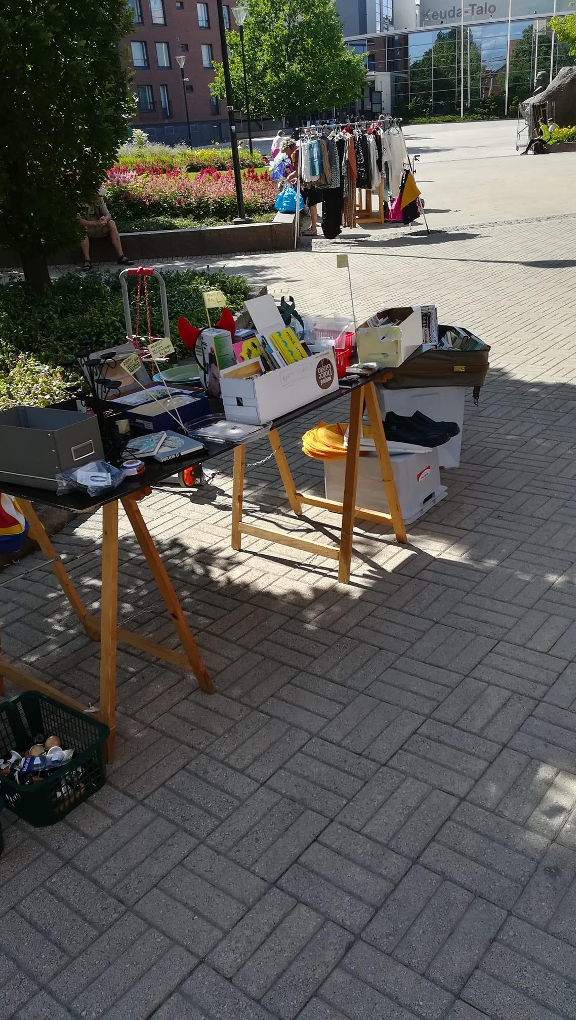 Pihakirpputori, jossa pöydällä ja rekillä vaatteita ja tavaraa.