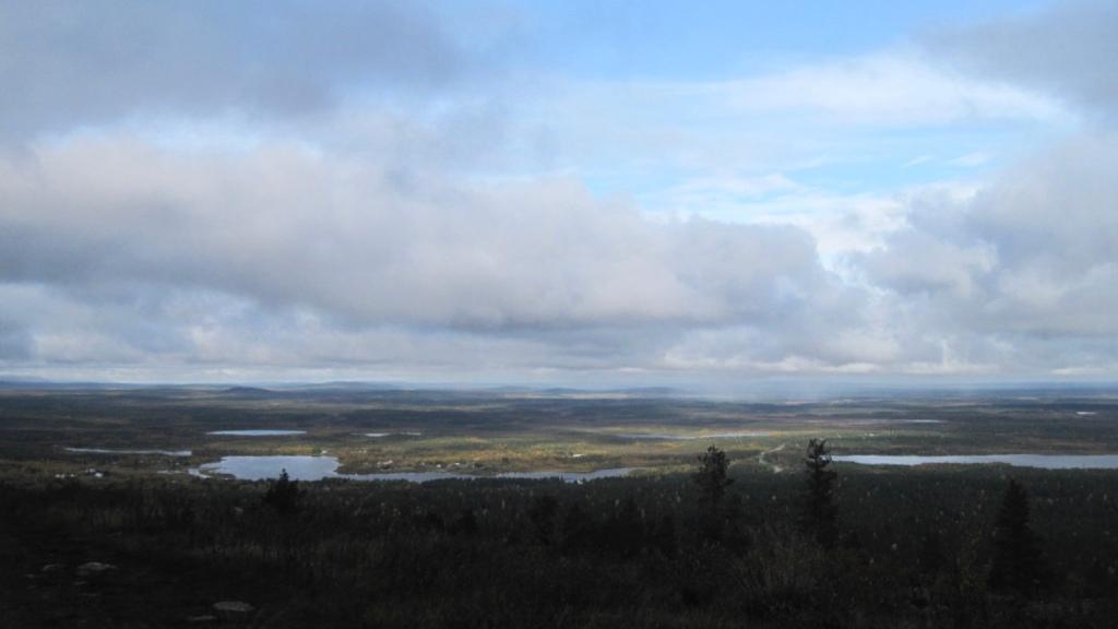 Ylhäältä maastosta kuvattu maisemakuva vesistöstä, metsästä ja taivaasta.