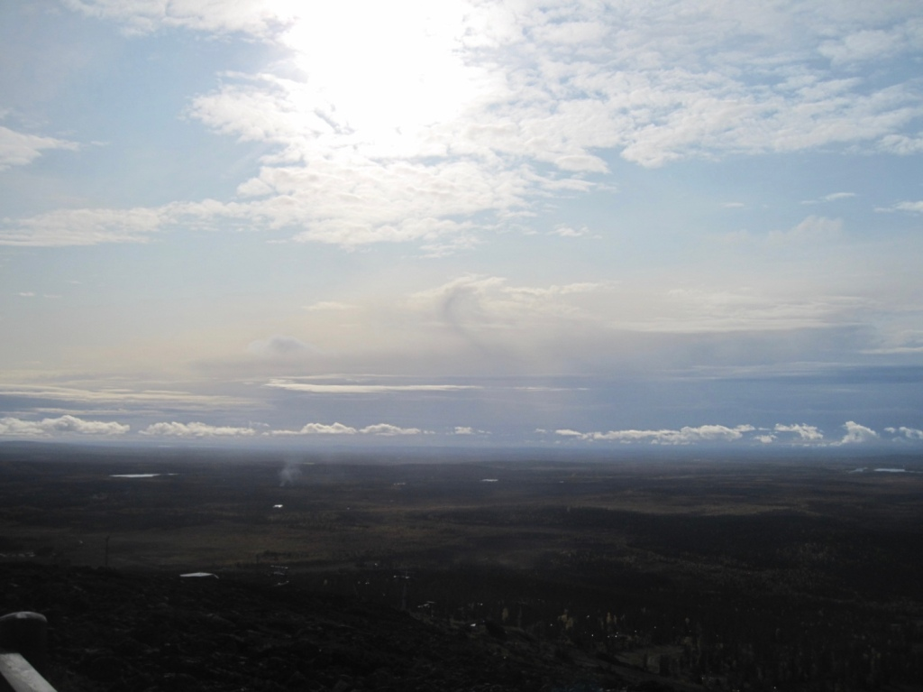 Ylhäältä päin kuvattu maa ja sininen taivas, jossa aurinko paistaa pilven läpi.