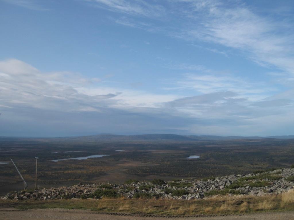 Taivas ja horisontissa kumpuilevaa maisemaa.