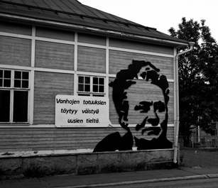 """Minna Canthin kuva piirretty talon seinään, jossa lukee, että """"Vanhojen totuuksien täytyy väistyä uusien tieltä""""."""