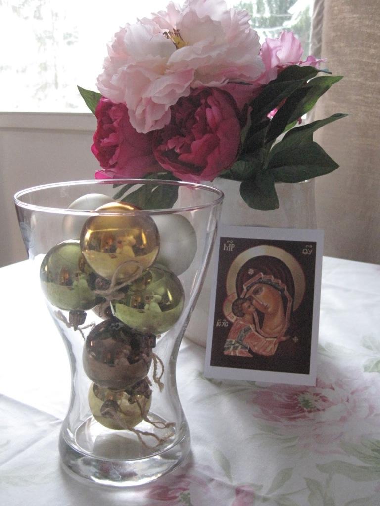 Kukkia, ikoni ja joulupalloja lasimaljakossa.