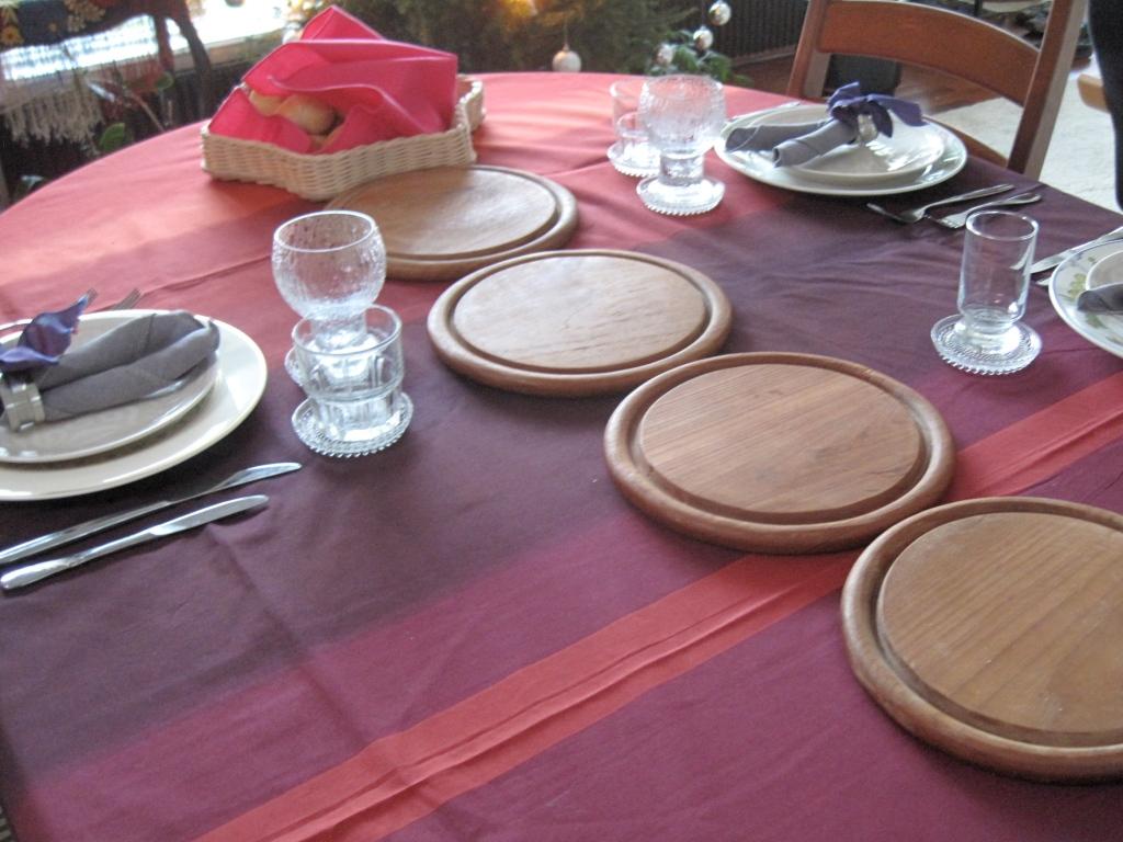 Joulun kattaus, valmiina vieraita varten. Pannunaluset ovat jo paikoillaan, kohta pöytään tuodaan laatikot ja muut herkut. Pöydässä joululiina ja pellavaiset servietit.