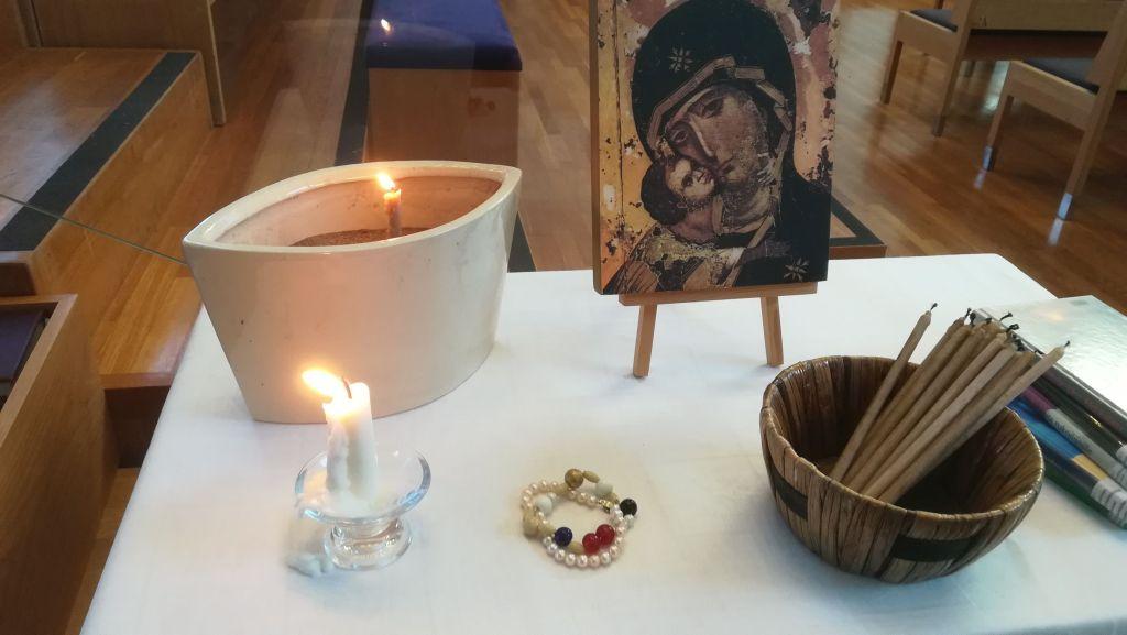 Kuvassa valkoisella pöydällä Hellyyden äiti -ikoni, tuohuksia, rukouskynttilöitä sytytettäväksi ja jo sytytettyinä selä Martin Lönnebon kehittelemät Frälsarkransen - rukoushelmet.