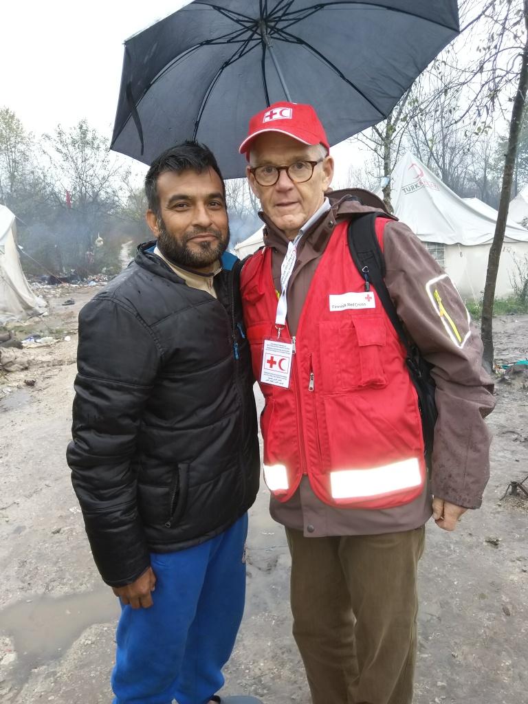 Kaksi miestä  sateenvarjon alla pakolaisleirillä.