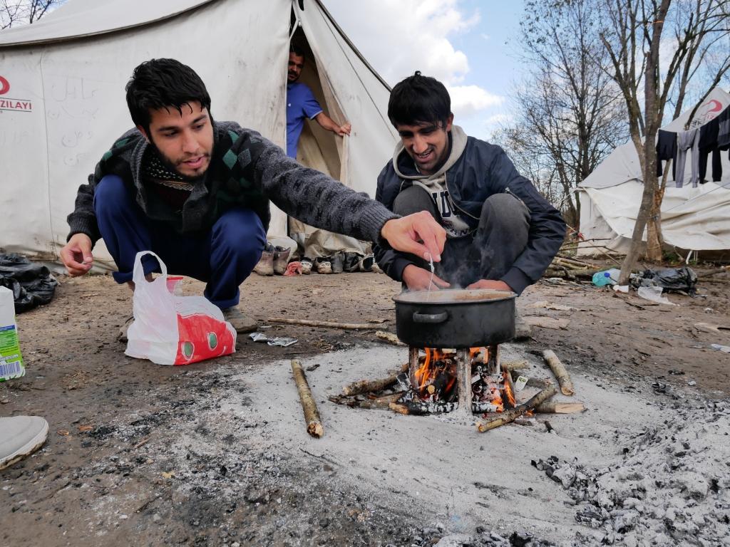 Kaksi afgaanimiestä keittää teetä pienessä kattilassa nuoriolla, taustalla pakolaisteltta.