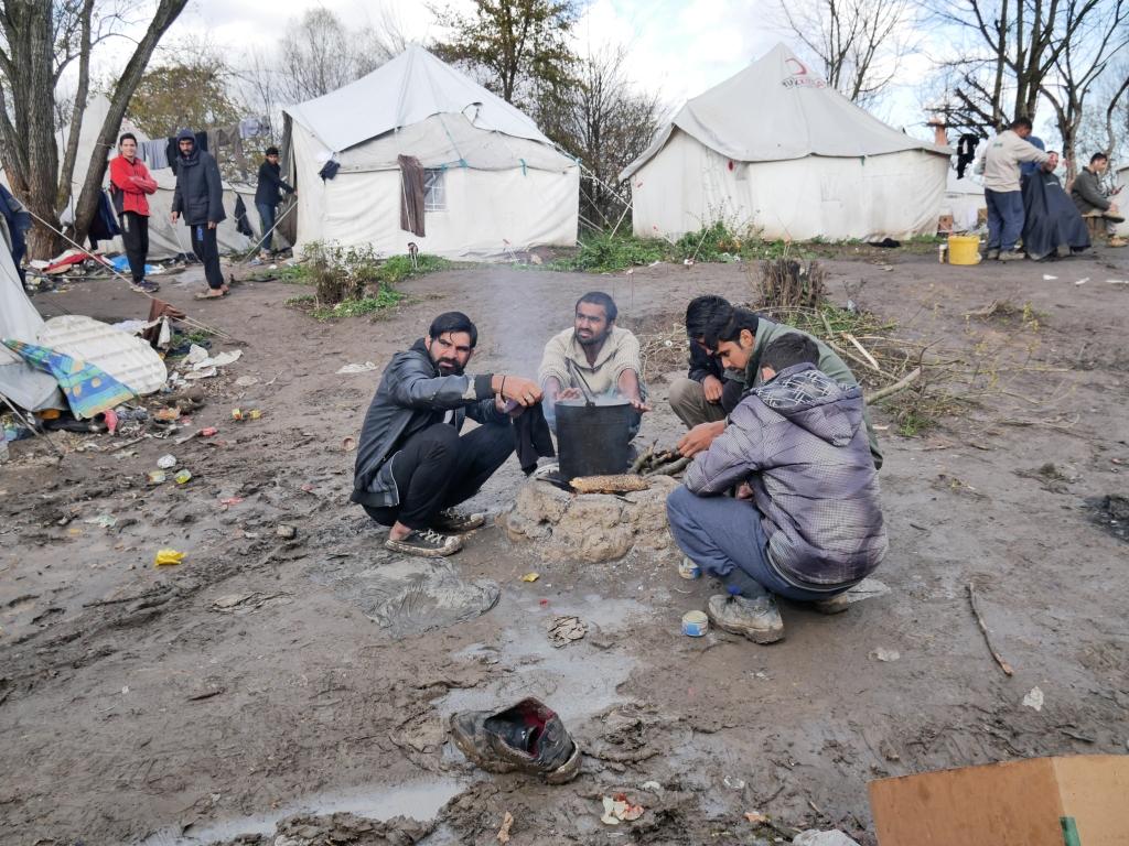 Miehiä nuotiolla keittämässä isossa kattilassa vettä, taustalla pakolaisleiritelttoja kuraisen metsän keskellä.