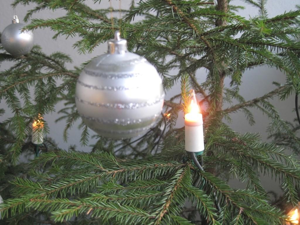 Joulukuusen oksalla hopeaa kimaltava pallo, jota kynttilä valaisee.