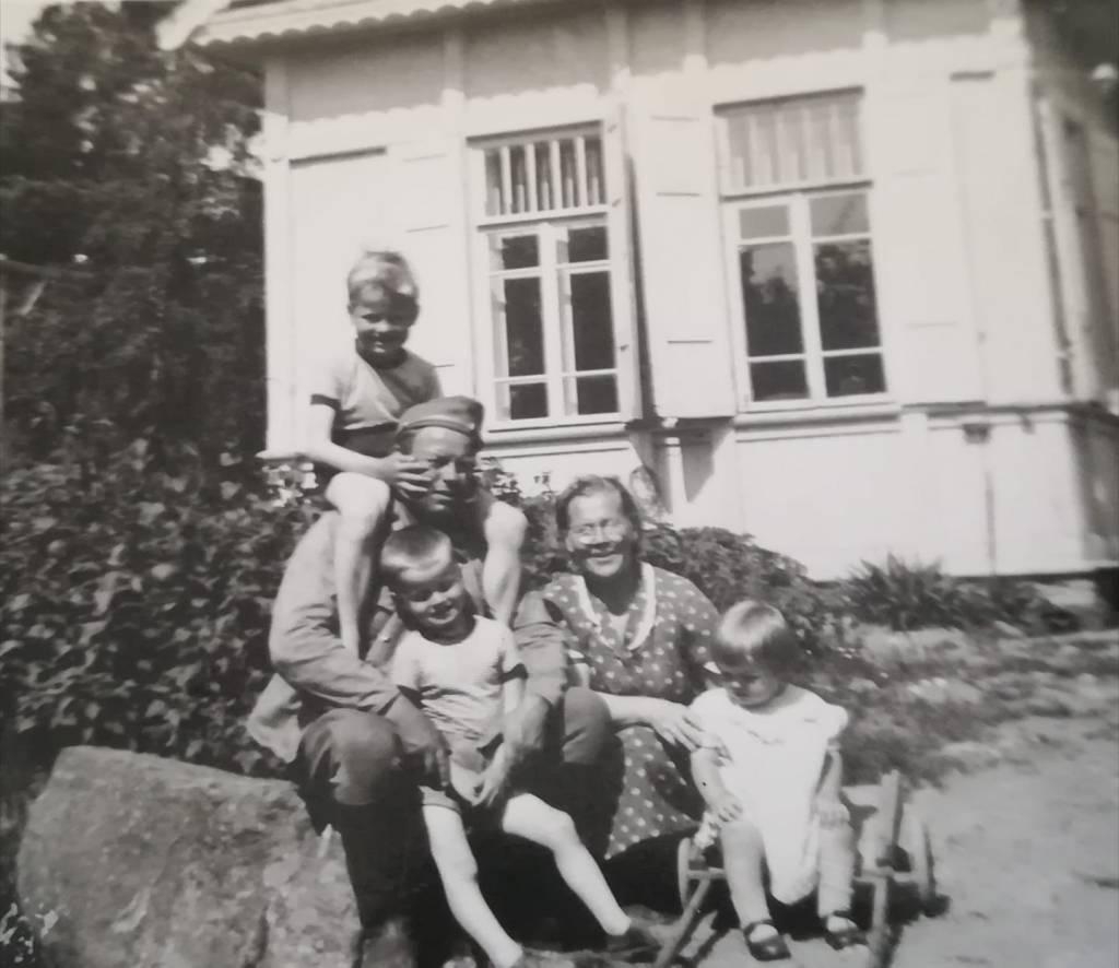 Vanhassa mustavalkokuvassa kesäisenä päivänä perhe, jossa isä, äiti ja kolme lasta istuvat talon pihalla.