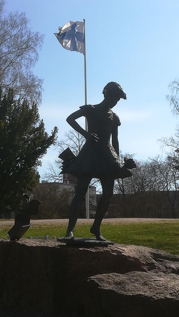 Kuvassa patsas, joka kuvaa nuorta tyttöä kesämekossaan paljasjaloin, taustalla liehuu Suomen lippu.