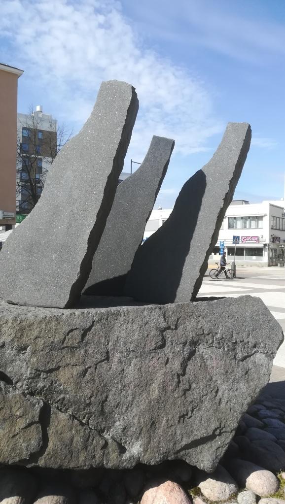 Kuvassa kolme vinoa kivijärkälettä ison kivijärkäleen päällä Häiväojan teoksessa Aurinko ja tuuli.