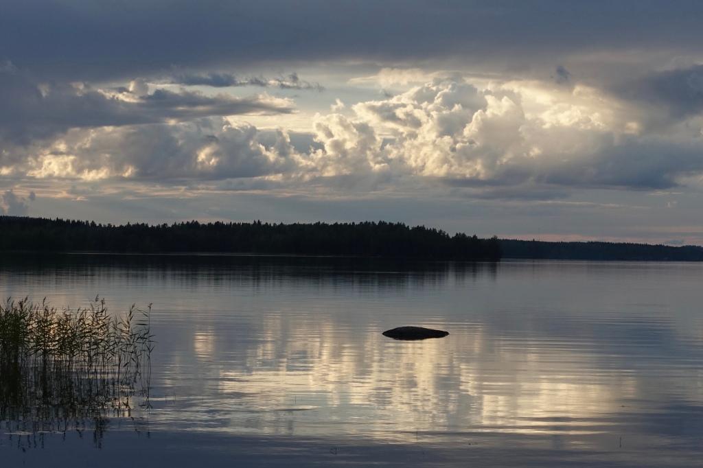 Iltapilvet heijastuvat järven pintaan. Taivas on lähellä, läsnä.