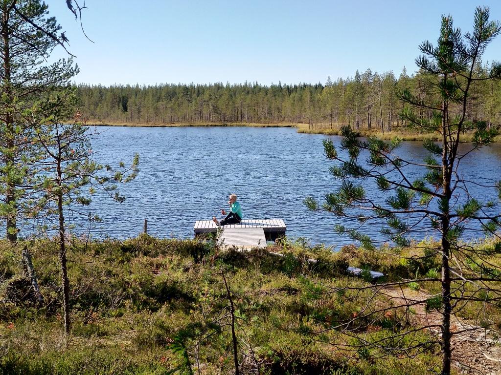 järvimaisema, jossa laiturilla istuu ihminen.