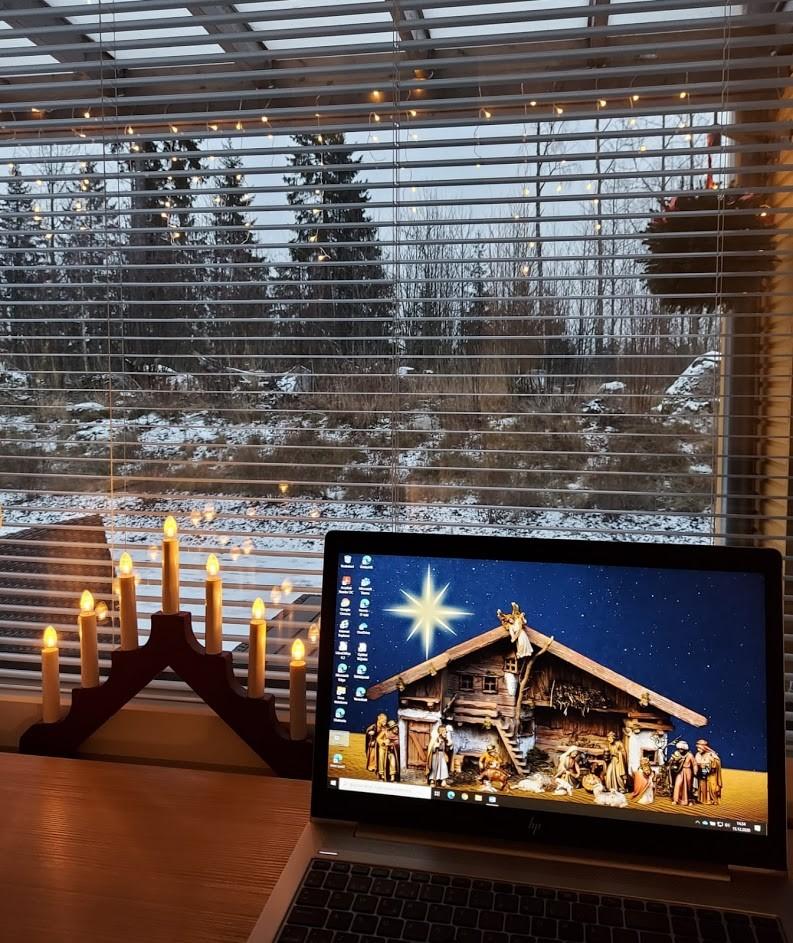 ikkunan edessäjoulukynttelikkö ja tietokone, jonka taustakuvana jouluseimi.