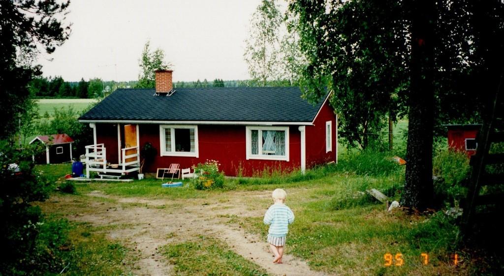 Punainen mökki, leikkimökki ja pihamaata alkukesällä. Pieni poika kävelee mäkeä alas.