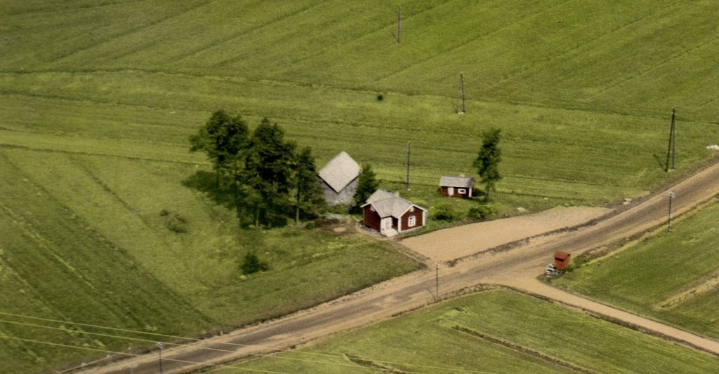Vanha ilmakuva mökkitontista, jossa näkyy punainen mökki, sauna ja vanha vaja peltojen keskellä.