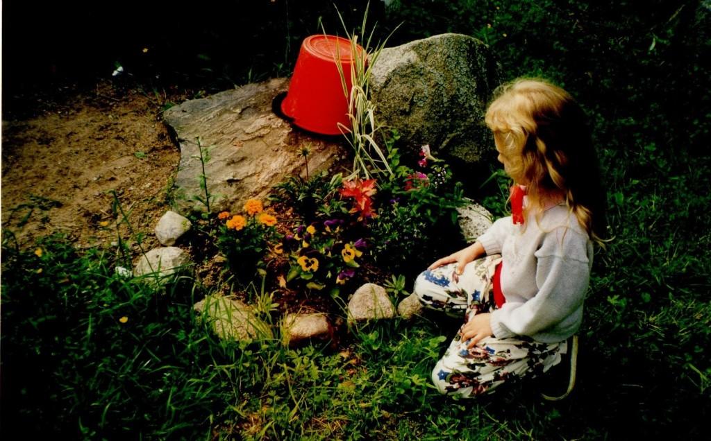 Emmi lapsena kyykistyneenä oman pienen kukkapenkkinsä viereen.