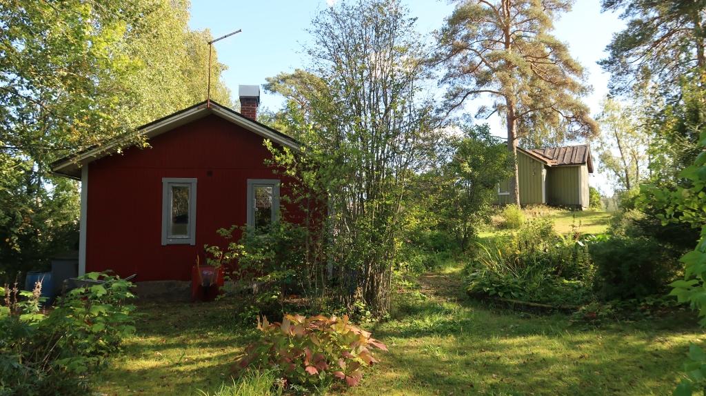 Alhaalta otettu kuva, jossa näkyy punainen mökki ja mäen päällä vihreä mökki vehreässä ympäristössä loppukesällä.